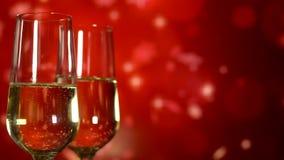 Due vetri con champagne scintillante sopra il fondo rosso di festa Fine in su video d archivio