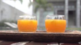 Due vetri con il coctail del succo d'arancia sul vassoio vicino allo stagno Donna che cammina dietro archivi video