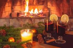 Due vetri con vin brul?, una candela, rami dell'abete con le decorazioni su una tavola di legno contro lo sfondo della a fotografia stock libera da diritti
