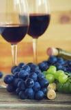 Due vetri con vino rosso, la bottiglia di vino, l'uva e gli ingorghi stradali del vino Immagini Stock