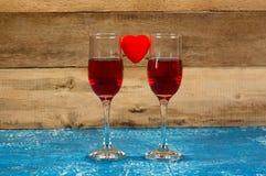 Due vetri con vino rosso su vecchio fondo di legno Festa Vale Fotografia Stock