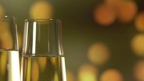 Due vetri con vino spumante sopra il fondo dorato di lampeggiamento dell'estratto archivi video
