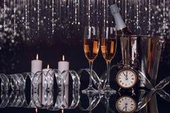 Due vetri del champagne, bottiglia, orologio e luci di Natale immagine stock