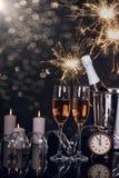 Due vetri del champagne, bottiglia, orologio e stelle filante immagini stock