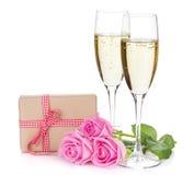 Due vetri del champagne, contenitore di regalo e rose di rosa fiorisce immagini stock