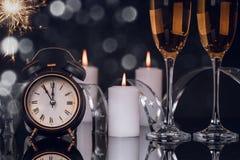 Due vetri del champagne, orologio, stelle filante e candele immagini stock