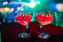 Due vetri del cocktail con ghiaccio in club con fondo vago variopinto Fotografia Stock