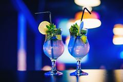 Due vetri del cocktail di Mojito con le paglie calce e menta al partito Immagini Stock