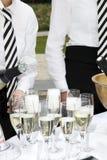 Due vetri del materiale di riempimento dei camerieri di champagne Immagine Stock