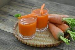 Due vetri del succo di carota e della carota matura saporita sul canestro di vimini sulla tavola di legno Fotografia Stock Libera da Diritti