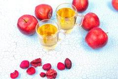 Due vetri del succo di mele e delle mele rosse su fondo di legno Immagine Stock