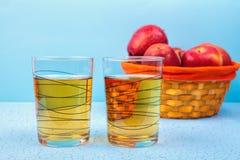 Due vetri del succo di mele e delle mele rosse su fondo di legno Fotografie Stock
