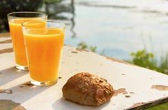 Due vetri del succo e del pane di arancia Fotografia Stock