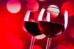 Due vetri del vino rosso contro bokeh rosso accende il fondo Fotografia Stock