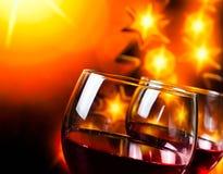 Due vetri del vino rosso contro il fondo dorato dell'albero delle luci Fotografia Stock Libera da Diritti