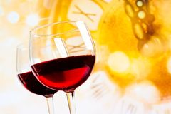 Due vetri del vino rosso contro il fondo dorato dell'orologio Immagini Stock
