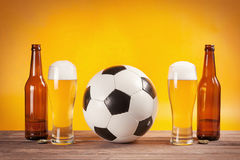 Due vetri della birra e delle bottiglie si avvicinano al pallone da calcio Immagini Stock Libere da Diritti