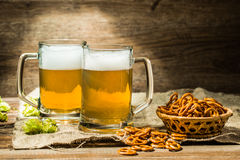 Due vetri della birra schiumano con il luppolo e le ciambelline salate Fotografia Stock Libera da Diritti