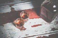 Due vetri della foto d'annata del whiskey, una bottiglia sulla barra Immagine Stock