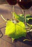 Due vetri delle foglie dell'uva e del vino rosso su una superficie di legno Fotografia Stock Libera da Diritti