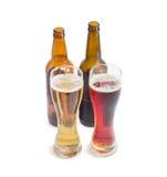 Due vetri di birra e due bottiglie di varia birra Fotografie Stock Libere da Diritti