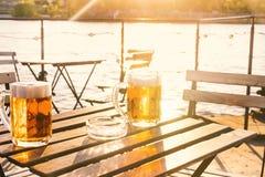 Due vetri di birra leggera con schiuma su una tavola di legno Su una barca Ricevimento all'aperto Sfondo naturale alcool Birra al Immagini Stock Libere da Diritti