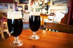 Due vetri di birra scura in una barra fotografia stock