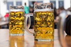 Due vetri di birra in tedesco biergarten il fondo Fotografie Stock