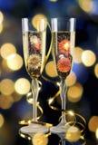 Due vetri di champagne con gli indicatori luminosi nei precedenti Fotografia Stock
