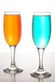 Due vetri di champagne con i liquidi colorati Fotografie Stock Libere da Diritti