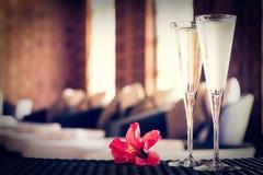Due vetri di champagne con il fiore rosso in una stazione termale bighellonano Ti della stazione termale Fotografia Stock