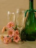 Due vetri di champagne con la bottiglia ed i fiori verdi su dorato Fotografia Stock Libera da Diritti
