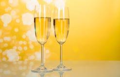 Due vetri di champagne con le bolle su giallo luminoso Fotografia Stock