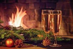 Due vetri di champagne, delle decorazioni, rami di albero di Natale e una candela su una tavola di legno davanti ad una combustio immagine stock