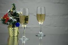 Due vetri di champagne fra l'abete si ramifica su un fondo scuro Un vetro con schiuma e un abbagliamento di luce riflessa, second fotografie stock libere da diritti