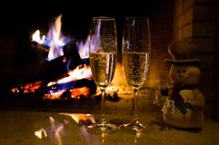 Due vetri di champagne vicino al fuoco bruciante Fotografie Stock Libere da Diritti