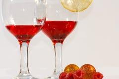 Due vetri di liquore, del limone e dei lamponi rossi Fotografia Stock Libera da Diritti