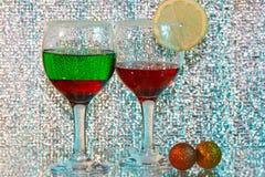 Due vetri di liquore rosso e verde e del limone Immagine Stock