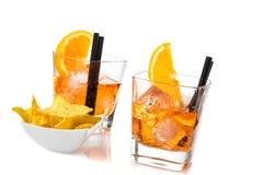 Due vetri di spritz il cocktail di aperol dell'aperitivo con le fette ed i cubetti di ghiaccio arancio vicino ai chip dei taci Fotografie Stock Libere da Diritti