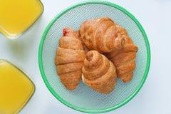 Due vetri di succo d'arancia e di due croissant con inceppamento su un fondo blu Spuntino utile Immagine Stock