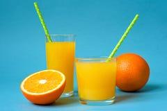 Due vetri di succo d'arancia e delle arance fresche sul fondo blu della tavola Immagini Stock