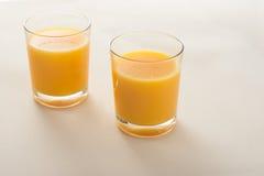 Due vetri di succo d'arancia sul fondo beige del tessuto Immagine Stock