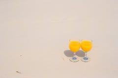 Due vetri di succo d'arancia sulla spiaggia bianca tropicale Fotografia Stock