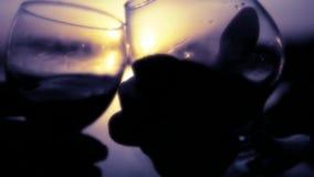 Due vetri di vetro con le varie bevande su un fondo di un declino all'acqua sono lavorati all'uncinetto circa a vicenda Movimento video d archivio