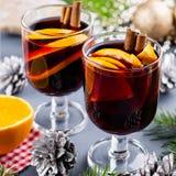 Due vetri di vin brulé caldo con le spezie e l'arancia affettata Il Natale beve con le decorazioni Vista superiore immagini stock libere da diritti
