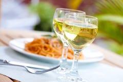 Due vetri di vino bianco con spaghetti in pomodoro Immagini Stock Libere da Diritti