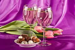 Due vetri di vino bianco, dei fiori e dei dolci Fotografia Stock