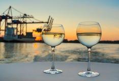 Due vetri di vino bianco fresco sulla tovaglia bianca con le strutture del porto e della nave da carico nel fondo vago Fotografie Stock