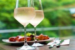 Due vetri di vino bianco raffreddato delizioso con lo spuntino nel restaur Fotografia Stock Libera da Diritti