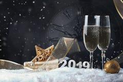 Due vetri di vino con champagne, l'orologio e gli ornamenti di Natale su un fondo nero con la riflessione fotografie stock